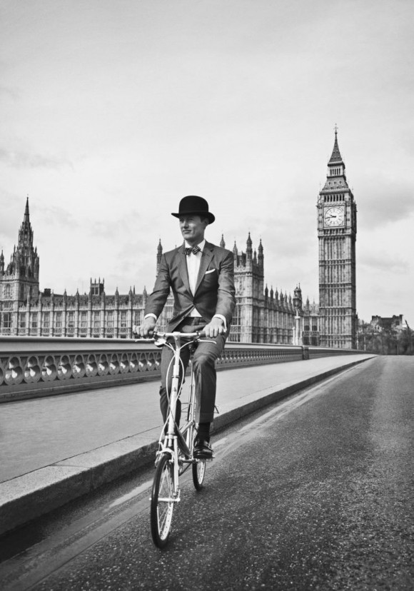 Bow tie, top hat & suit. Man riding funny bike in london black & white photography. Clothing by Hackett