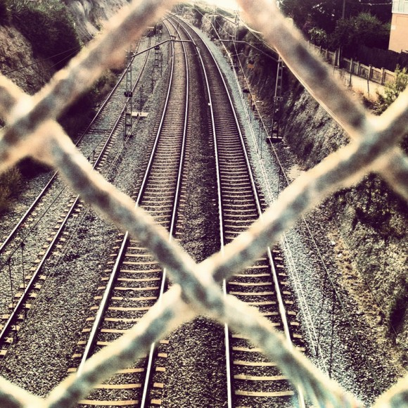 pov-train-tracks-through-a-rusty-metal-fence