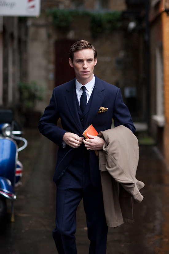 Navy Tie Navy Three Piece Suit Holding a Book and Coat over arm