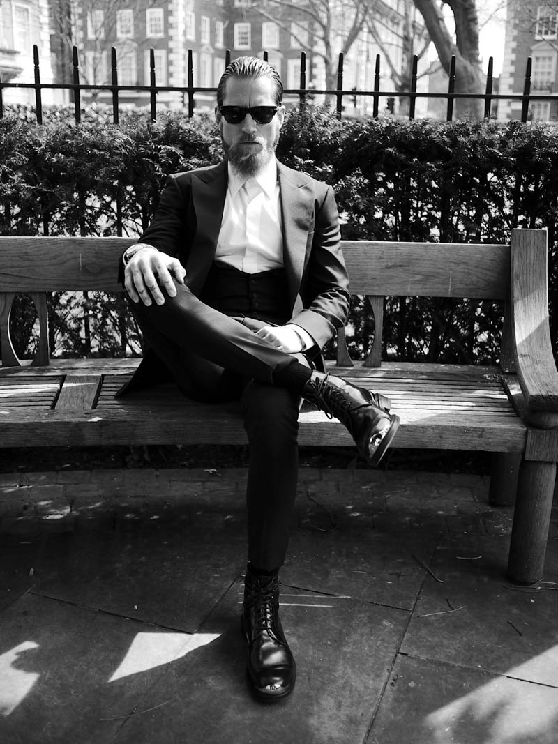 Justin O'Shea Black & White suit leg cross park bench